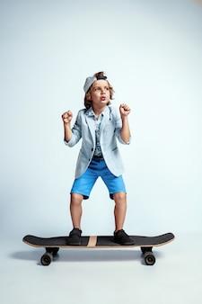 白いスタジオの壁にカジュアルな服を着てスケートボードでかなり若い男の子