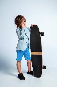 白い壁にカジュアルな服装でスケート ボードに乗ったかなりの少年。乗って幸せそうです。明るい顔の感情を持つ白人の男性未就学児。子供時代、表現、楽しみ。