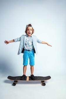 白い壁にカジュアルな服を着たスケートボードのかわいい少年。乗って幸せそうに見えます。明るい顔の感情を持つ白人男性の未就学児。子供の頃、表現、楽しんで。