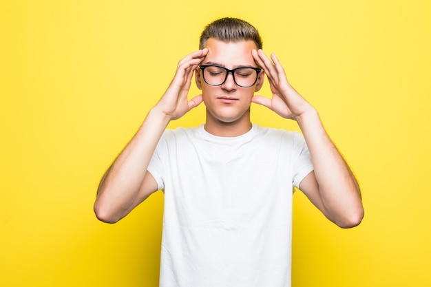 Pretty young boy shows thinking sign dressed up in white t-shirt and transperent glasses isolated on yellow