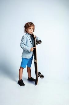 Ragazzo abbastanza giovane su skateboard in abiti casual sulla parete bianca dello studio