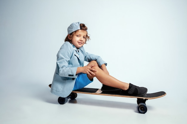 Pretty young boy on skateboard in casual clothes on white studio