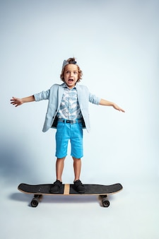 Pretty young boy on skateboard in casual clothes on white  wall. riding and looks happy. caucasian male preschooler with bright facial emotions. childhood, expression, having fun.