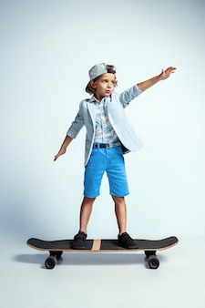 Pretty young boy on skateboard in casual clothes on white