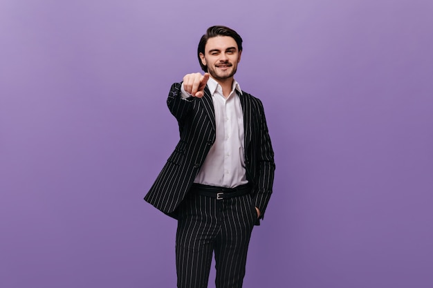 Pretty young boy with brunette hair, light shirt and dark striped suit looking and pointing at front isolated on violet wall