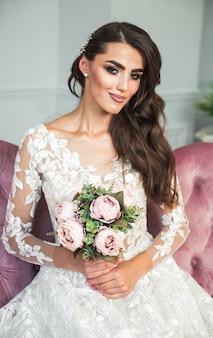 ブライダルブーケを持って白いウェディングドレスでかなり若い花嫁。ウェディングドレスの豪華な花嫁。エレガントな高価なインテリアで豪華なウェディングドレスで美しいブルネットの女性。髪型・美容