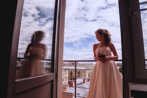 街と雲と青い空の素晴らしい景色を望むバルコニーにいるかなり若い花嫁。晴れた結婚式の日の花嫁の朝。花束を手にした幸せな花嫁が新郎を待っています。著作権スペース