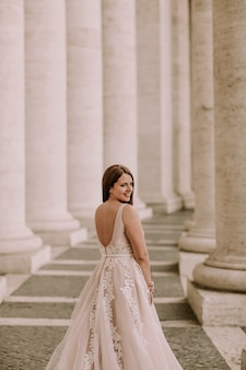 Pretty young bride in wedding dress in the vatican colonnade