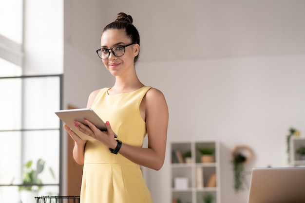 사무실 환경에서 카메라 앞에서 터치 패드를 사용하여 안경과 드레스에 꽤 젊은 갈색 머리 사업가