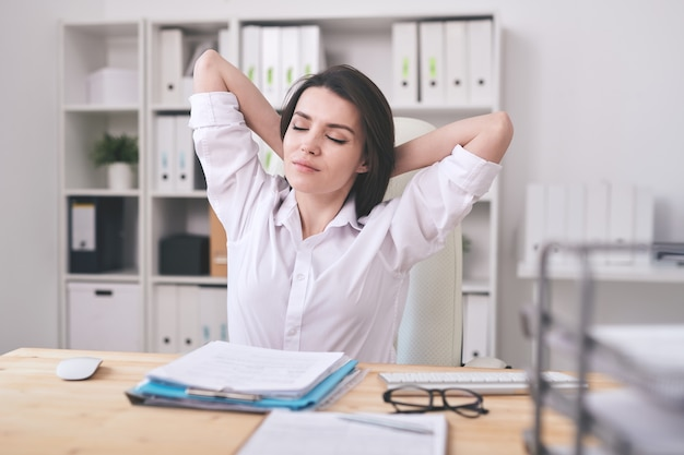 肘掛け椅子に座って、オフィス環境でリラックスして頭の後ろに彼女の手を持つかなり若いブルネットの実業家またはマネージャー