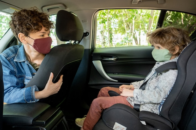 Pretty young brunette female in protective mask sitting in car and looking at her cute little son on backseat while going to supermarket