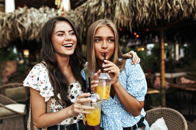 흰색 꽃무늬 블라우스를 입은 예쁜 젊은 갈색 머리 소녀와 파란색 탑 음료를 입은 무두질한 매력적인 금발의 여성이 밖에서 맛있는 레모네이드를 마십니다