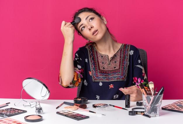 화장 도구를 들고 테이블에 앉아 있는 예쁜 브루네트 소녀, 복사 공간이 있는 분홍색 벽에 격리된 메이크업 브러시로 얼굴을 붉히며