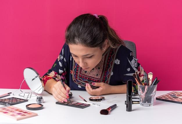 Bella ragazza bruna seduta al tavolo con strumenti per il trucco che tiene l'eyeliner e guarda la tavolozza dell'ombretto