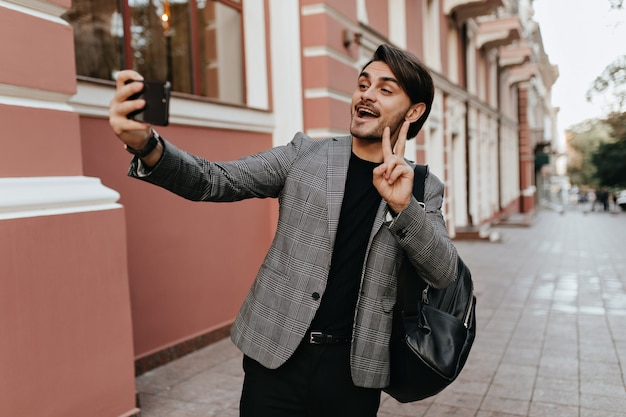 Pretty young brunette-haired man wearing black t-shirt and grey blazer, backpack, saluting and making selfie on phone in daylight street