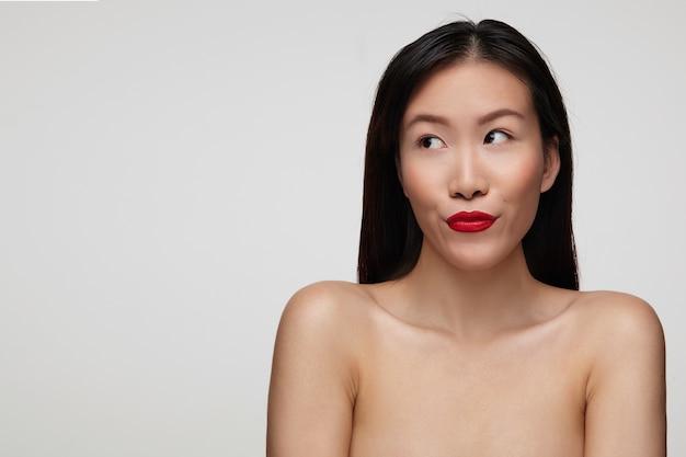 カジュアルな髪型のかなり若いブルネットの女性は、手を下に向けて白い壁の上に立って、口を横に見ながら彼女の赤い唇をすぼめます