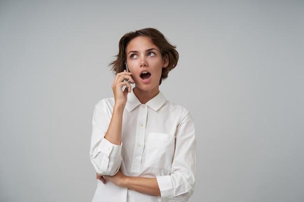 Bella giovane signora bruna con taglio di capelli corto conversando al telefono e ricevendo notizie sorprendenti, indossa una camicia bianca in piedi