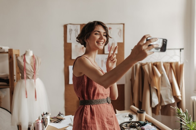 Pretty young brunette short-haired woman in linen red dress with black belt smiles, takes selfie, shows peace sign and poses in office of fashion designer