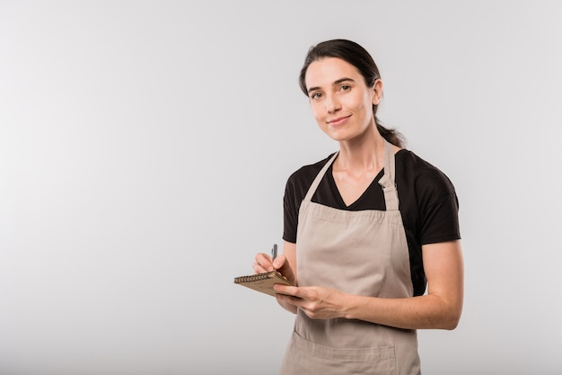 Pretty young brunette waitress in apron making notes about order in notepad while standing in front of camera in isolation