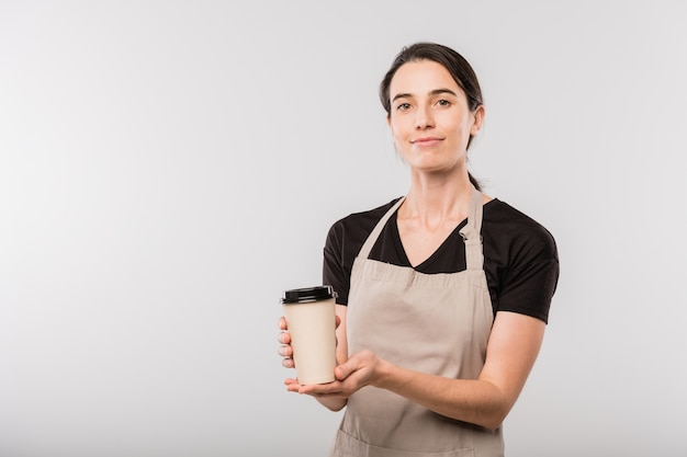 Pretty young brunette waitress of cafe in apron passing you disposable glass with hot coffee while standing in isolation