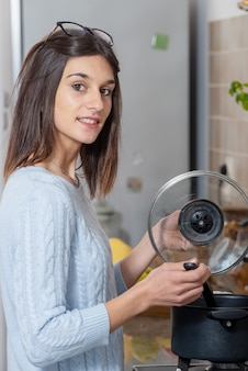 Pretty young brunette woman cooking in the kitchen