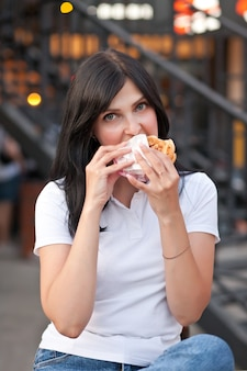 꽤 젊은 갈색 머리 여자 거리에서 야외 햄버거를 먹고.