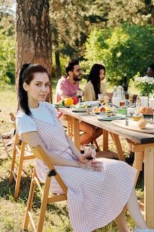 Довольно молодая брюнетка женщина в повседневной одежде, сидя на стуле