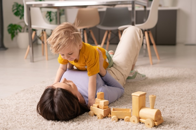 Pretty young brunette woman lying on fluffy rug on the floor and playing with her adorable little son while staying at home during quarantine