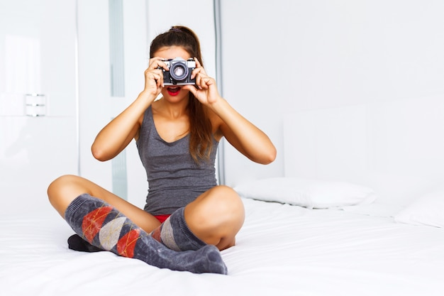 Pretty young brunette woman sitting at big white bed and taking picture on vintage retro camera