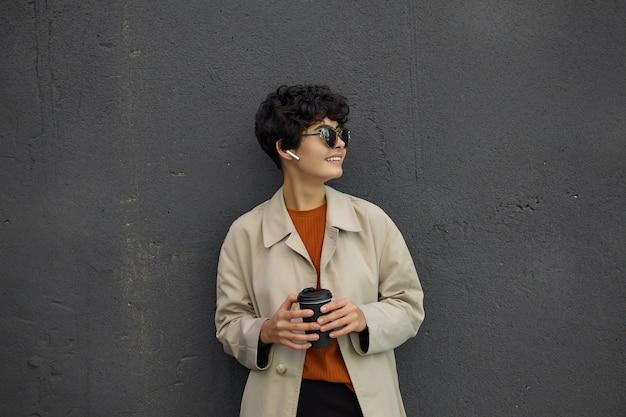 Piuttosto giovane donna bruna con acconciatura casual tenendo il caffè da asporto e guardando da parte positivamente, indossando abiti eleganti mentre si sta in piedi sulle mura nere della città