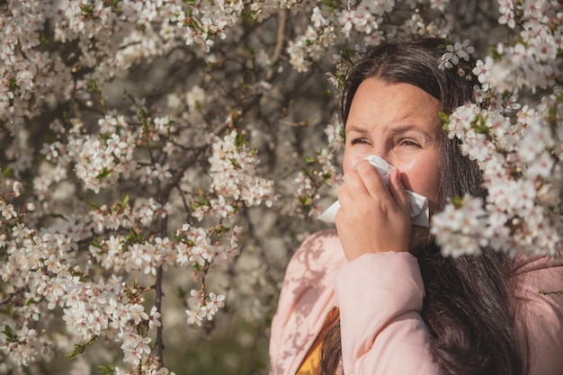 Pretty young brunette woman with strong allergy reaction during spring time, sneezing  with a paper tissue, healthcare concept