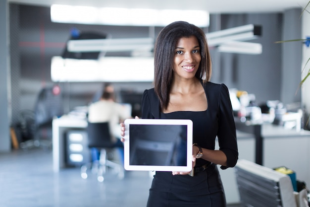 Pretty, young business lady in black strong suite hold tablet