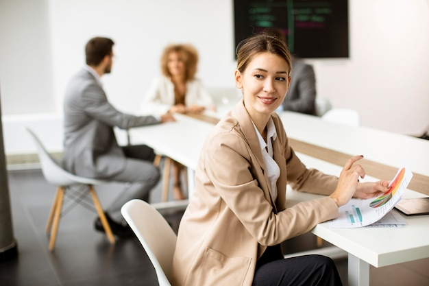 Pretty young business woman analyzing business chart in front of her team at the office