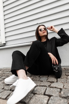 Pretty young business woman fashion model in white shoes in stylish black clothing with handbag straightens fashion sunglasses near wooden wall in city. beaty girl in casual wear sit on stone tile.