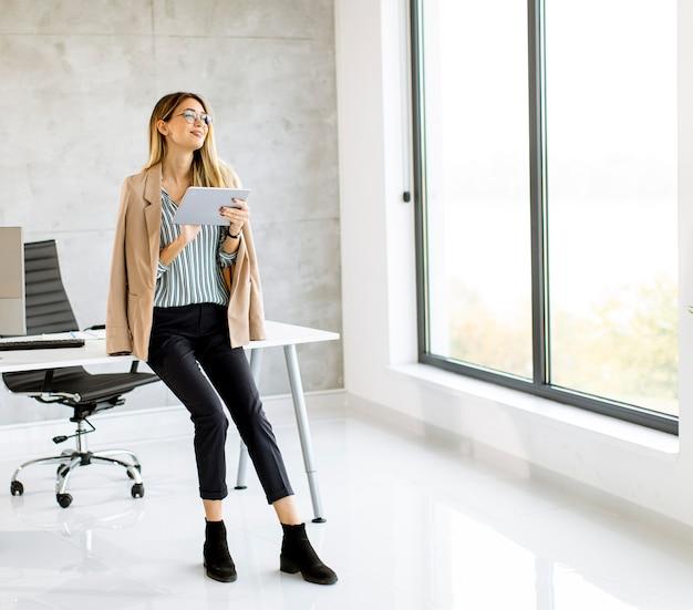Довольно молодая деловая женщина, держащая цифровой планшет и стоящая в современном офисе