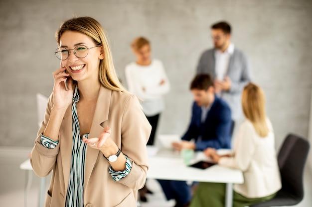 Довольно молодая деловая женщина, стоящая в офисе и подающая в суд на мобильный телефон перед своей командой