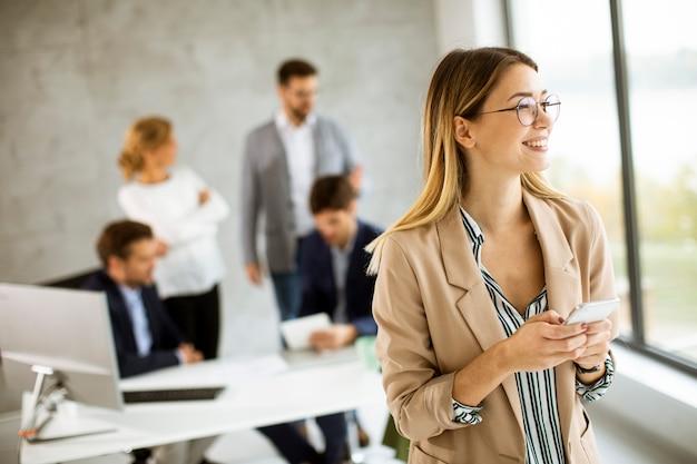 사무실에 서서 그녀의 팀 앞에서 휴대 전화를 고소하는 꽤 젊은 비즈니스 우먼