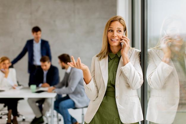 Довольно молодая деловая женщина, стоящая в офисе и использующая мобильный телефон перед своей командой Premium Фотографии