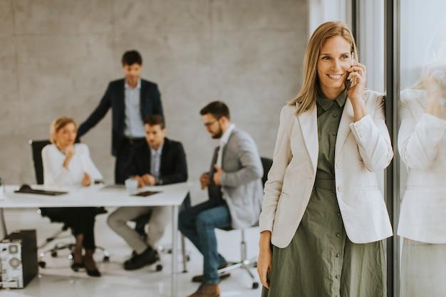 사무실에 서서 그녀의 팀 앞에서 휴대 전화를 사용하는 꽤 젊은 비즈니스 우먼