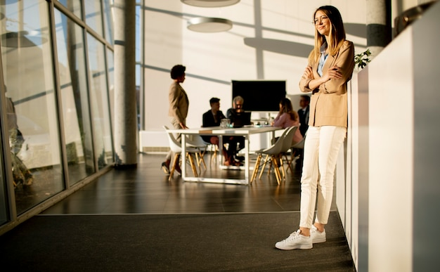 Pretty young business woman standing in the office and using mobile phone in front of her team