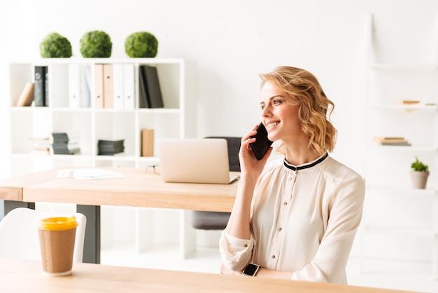携帯電話で話しているかなり若いビジネス女性。