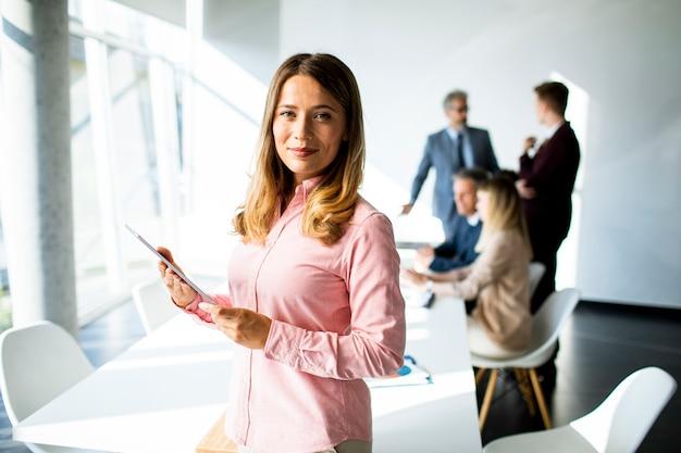Довольно молодая деловая женщина с помощью цифрового планшета в офисе
