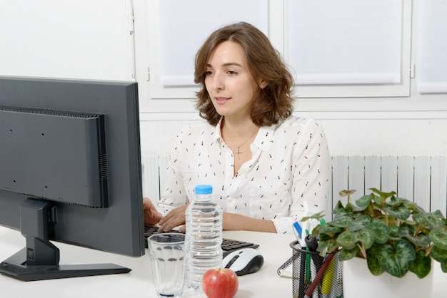 Pretty young business woman working at pc in office