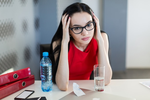 Pretty, young businesslady in red dress and glasses sit at the table and work