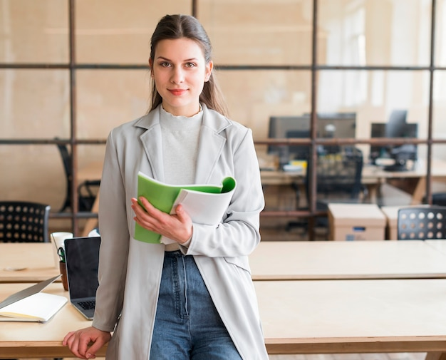 Pretty young businesswoman leaning on desk holding book looking at camera in office