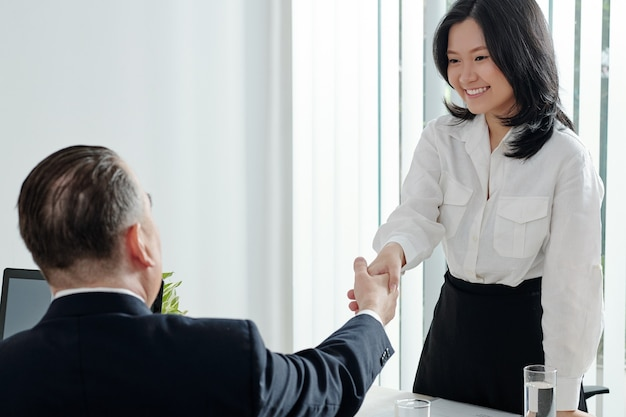 Pretty young businesswoman shaking hands of head of department before meeting or job interview