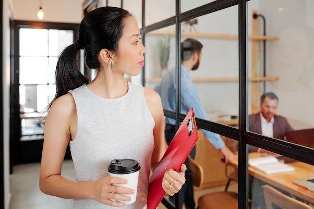 Довольно молодая бизнес-леди с чашкой кофе и папкой с документами проходит мимо конференц-зала со стеклянными стенами и смотрит на говорящих коллег