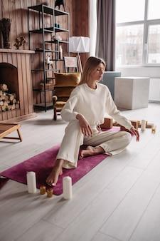 週末に居心地の良い家のインテリアで自然なマットの上に座ってリラックスして瞑想するかなり若い穏やかな女性。女性の健康。