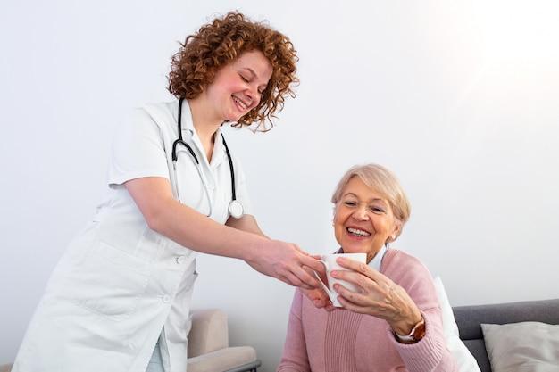 年配の幸せな女性に午後のお茶を提供するかなり若い介護者。若い看護婦さんが自宅で高齢者の世話をしています。