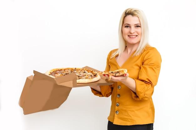 배달 종이 상자에 맛있는 피자와 함께 꽤 젊은 캐주얼 여자. 흰색 배경에 고립